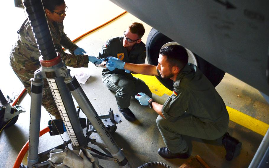 Tech Sgt. Hazel Cochran, left, hands safety goggles to German military academy cadet Tom Palzer before he and fellow cadet Tim Herbst, center, change the tires on a C-130J at Ramstein Air Base on July 15, 2021. The future Luftwaffe pilots are the first from the German military academy to train with U.S. Air Force maintenance crews at Ramstein Air Base.