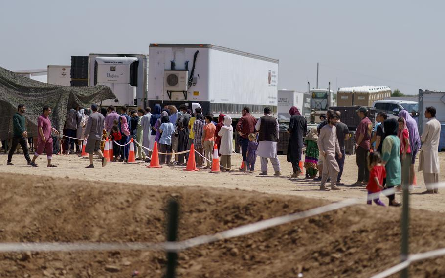 Afghan refugees line up for food outside a dining hall at Fort Bliss' Doña Ana Village where they are being housed in Chaparral, N.M., Friday, Sept. 10, 2021.