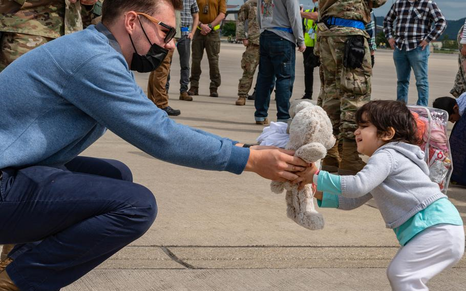 U.S. Air Force Airman Andrew Markos, 721st Aerial Port Squadron passenger service specialist, hands a Teddy bear to an Afghan evacuee at Ramstein Air Base, Germany, Aug. 24, 2021. U.S. airmen and volunteers have been working to deliver clothing, toys, water and other items to around 14,500 evacuees who have arrived at  Ramstein since August 17, 2021.