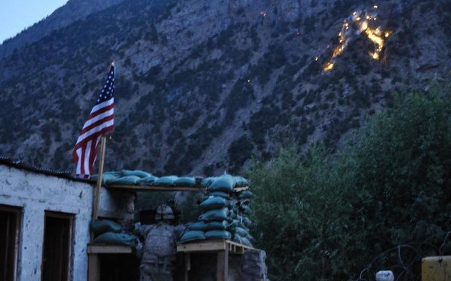 Adam Holroyd looks on as ordnance explodes on a hillside overlooking the Afghan village of Barg-e Matal in the northeastern province of Nuristan in the summer of 2009. An outbuilding that housed hundreds of rocket-propelled grenades and other ammunition, which was later hit by an RPG during an attack, is on the left.