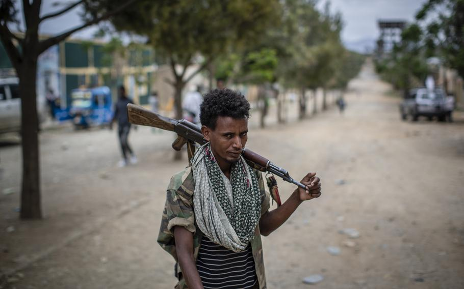 A fighter loyal to the Tigray People's Liberation Front walks along a street in the town of Hawzen, then-controlled by the group, in the Tigray region of northern Ethiopia, on May 7, 2021.