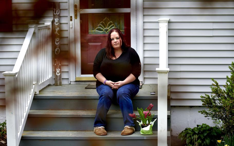 Tasha Clark, who suffers from long-haul COVID, sits on the steps of her home in Milford, Conn., on May 3, 2021.