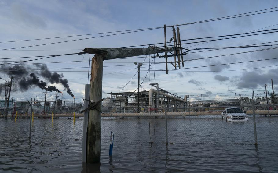 Broken power lines, destroyed by Hurricane Ida, are seen along a highway near a petroleum refinery on August 30, 2021 outside LaPlace, La.