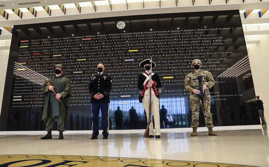 Soldiers from Fort Myer, Va., dressed in uniforms from various eras, stand in front of a display listing the Army's campaigns in the lobby of the National Museum of the United States Army on its reopening day, June 14, 2021, which is also the service's 246th birthday.