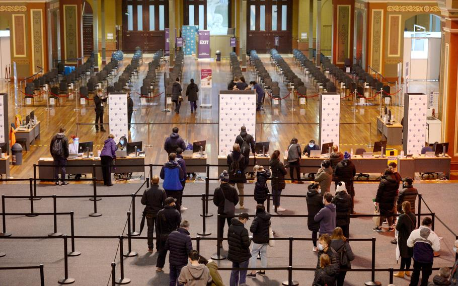 People wait in line to register at a COVID-19 vaccination center set up at the Royal Melbourne Exhibition Centre in Melbourne, Australia, on June 8, 2021.