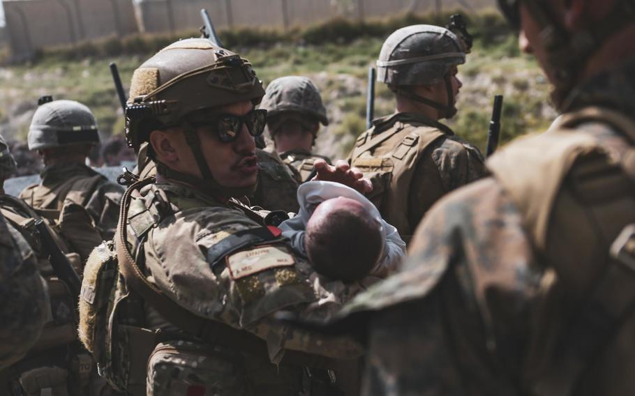 A U.S. service member comforts an infant during an evacuation at Hamid Karzai International Airport, Kabul, Afghanistan, Aug. 20, 2021.