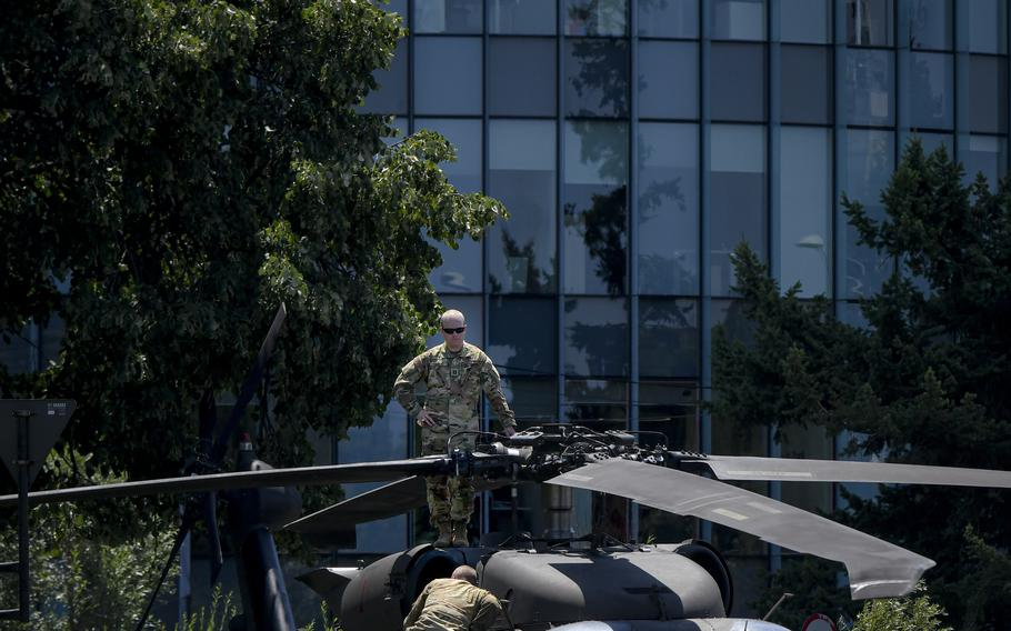 A U.S serviceman inspects the blades of an U.S military Black Hawk helicopter following an emergency landing on a busy boulevard in Bucharest, Romania, Thursday, July 15, 2021.