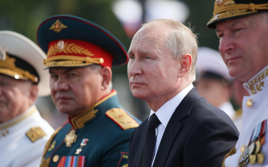 Vladimir Putin, Russia's president, center, sits alongside Sergei Shoigu, Russia's defense minister, second left, during the Russian Navy day in St. Petersburg, Russia, on July 28, 2019.