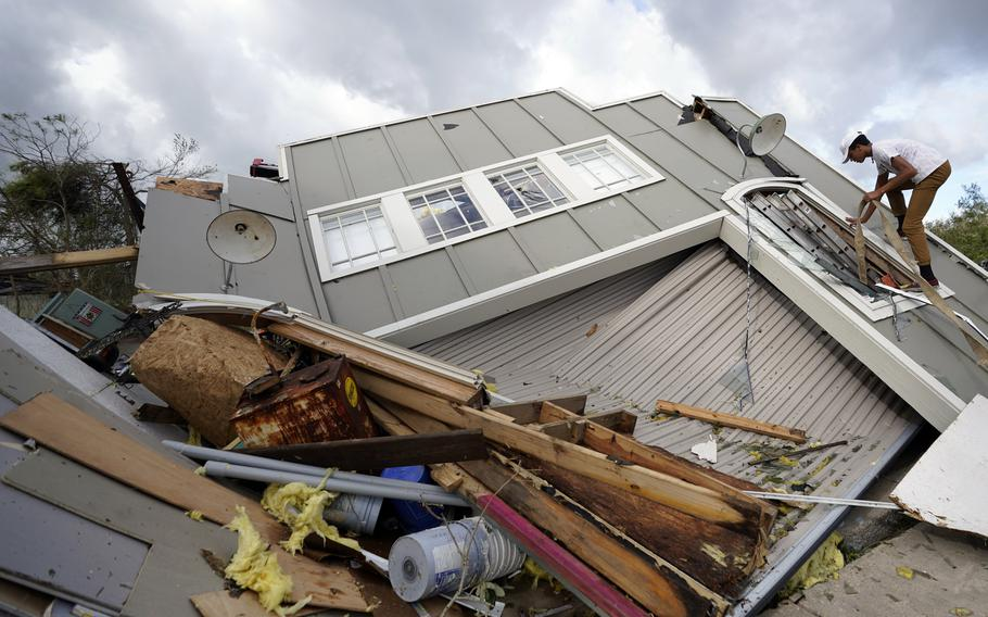 Jeremy Hodges climbs up the side of his family's destroyed storage unit in the aftermath of Hurricane Ida, Monday, Aug. 30, 2021, in Houma, La.