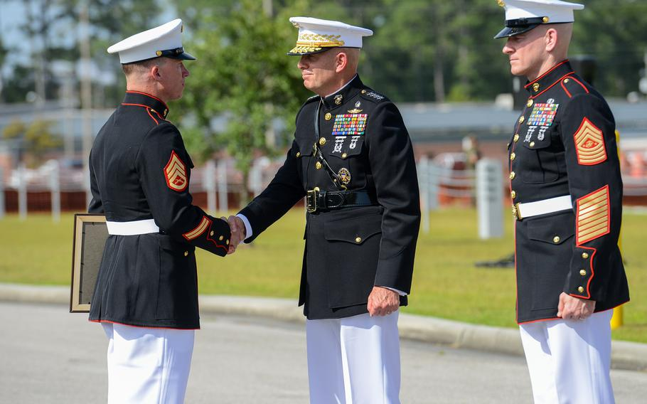 Marine Raider Staff Sgt. Nicholas Jones is presented the Navy Cross by Gen. David Berger, the Marine Commandant, on Thursday, Aug. 26 at Camp Lejeune, as Sgt. Maj. of the Marine Corps Troy Black looks on. Jones, a member of the elite 2nd Marine Raider Battalion was awarded the nation's second highest medal for battlefield heroics for his actions in a deadly fight with Islamic State group militants in Iraq in March 2020.