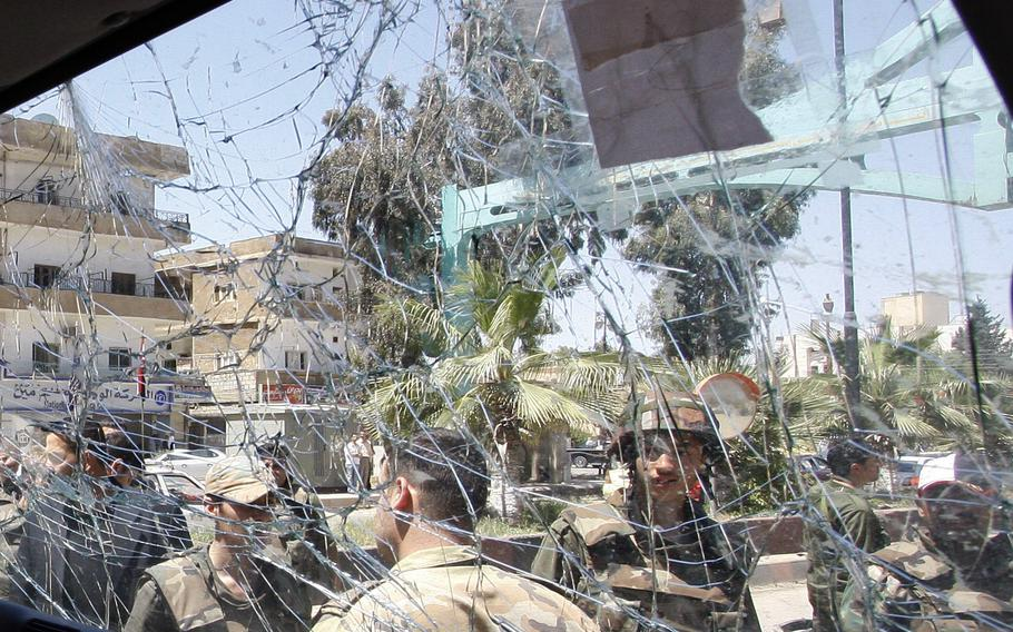 Syrian army soldiers, are seen through a damaged military truck window in Daraa city, Syria, on May 9, 2012. According to reports on Wednesday, Sept. 8, 2021, Syrian forces entered Daraa as part of a truce negotiated by Russia to end fighting in the city.