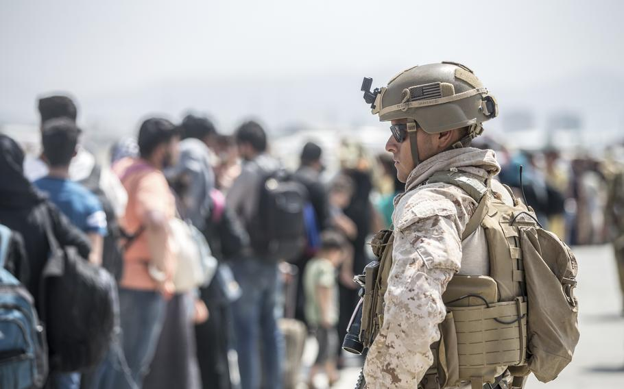 In this Aug. 22, 2021, image provided by the U.S. Marine Corps, a Marine with Special Purpose Marine Air-Ground Task Force-Crisis Response-Central Command provides assistance during an evacuation at Hamid Karzai International Airport in Kabul, Afghanistan.