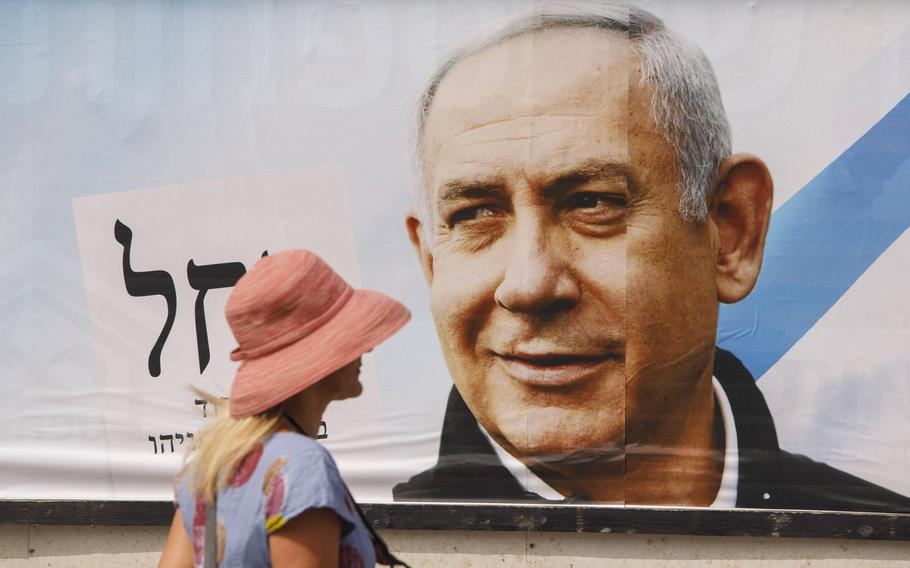A pedestrian passes an election campaign billboard for Benjamin Netanyahu, Israel's prime minister and the leader of the Likud party, in Tel Aviv, Israel, on March 15, 2021.