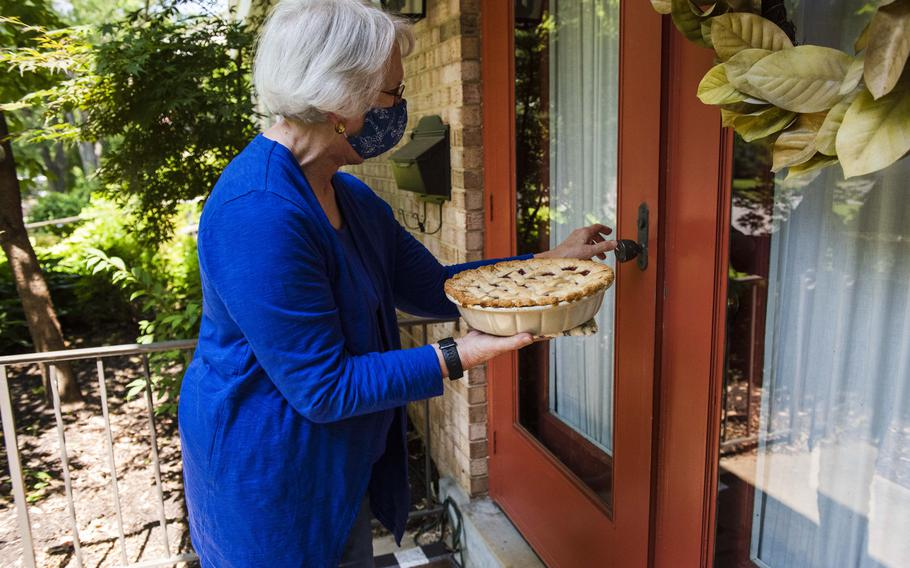 Betty Douglass, 80, drops off a cherry pie Friday for daughter Kim Marin's 51st birthday at her home, while Marin and her daughter are self-isolating.
