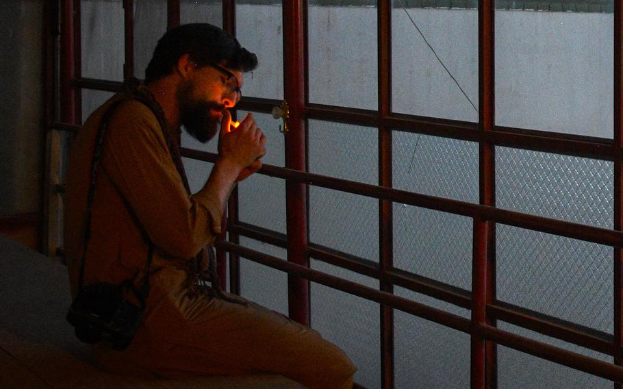Chris Jones, who fought in Helmand province during two tours as a Marine, lights a cigarette as he watches the sun set on a return trip to the province in 2019. Jones said the process of trying to help evacuate Afghans who worked with the U.S. government brought back memories of his time in Afghanistan, along with feelings of helplessness and regret for not being able to save people.
