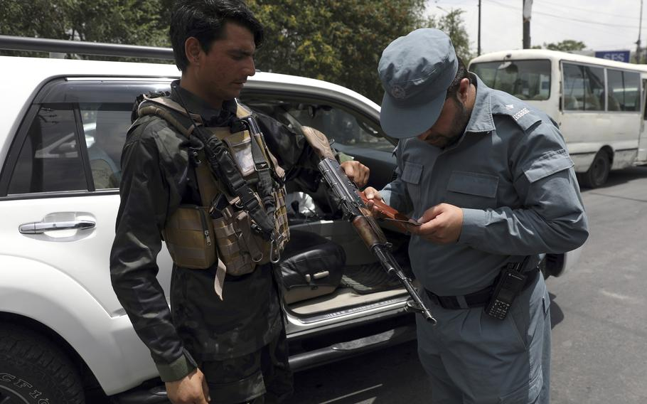 An Afghan policeman checks the documentation of a gun owner, at a temporary checkpoint in Kabul, Afghanistan, Sunday, July 4, 2021.