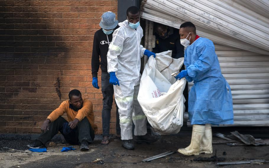 A family member watches on as police forensics officers carry the body his brother who was found inside a burned shop, in Johannesburg, South Africa, Sunday, July 11, 2021.