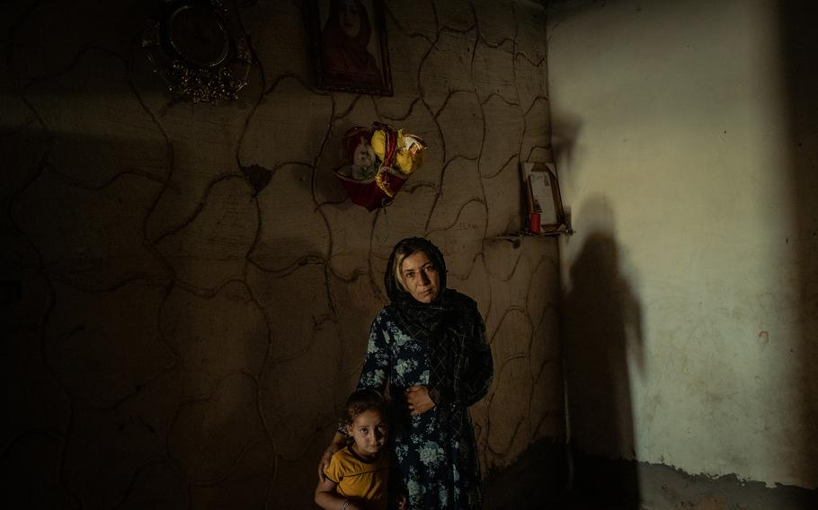 Rusil Latif al-Khadir, 4, and Hiyam Latif al-Khadir, 22, the daughter and sister, respectively, of Hind Latif al-Khadir, stand beneath a portrait of her at their home in Dashisha, close to Syria's border with Iraq.