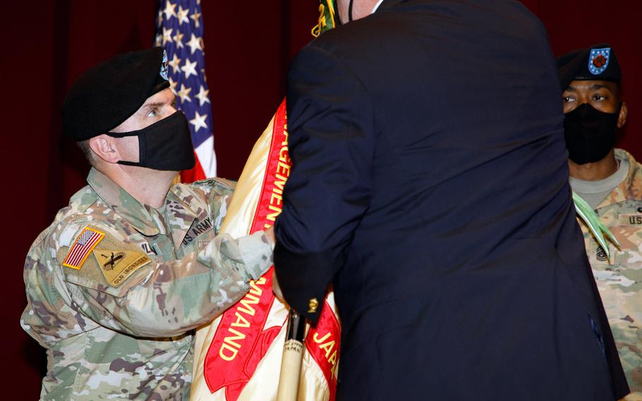 Col. Christopher Tomlinson accepts the U.S. Army Garrison Japan flag during a change-of-command ceremony at Camp Zama, Japan, Tuesday, July 20, 2021. The outgoing commander, Col. Thomas Matelski, is moving to Indo-Pacific Command in Hawaii to become chief of the Civil Affairs Planning Team, J9.