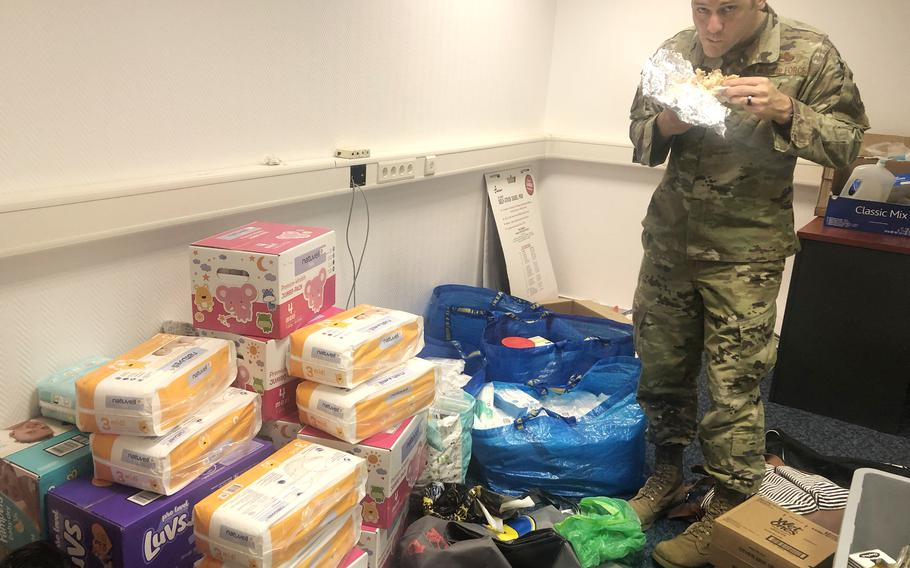Andrew Wilder, an Air Force first sergeant, takes a late-night bite to eat in a room filled with toiletries and baby items donated at Ramstein Air Base in Germany, August 19, 2021. Donations were collected within hours for evacuees who could arrive at the base from Afghanistan.