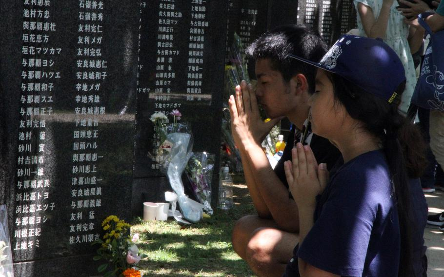Children pray for those killed in the Battle of Okinawa during the island's annual Irei no Hi ceremony on June 23, 2018.