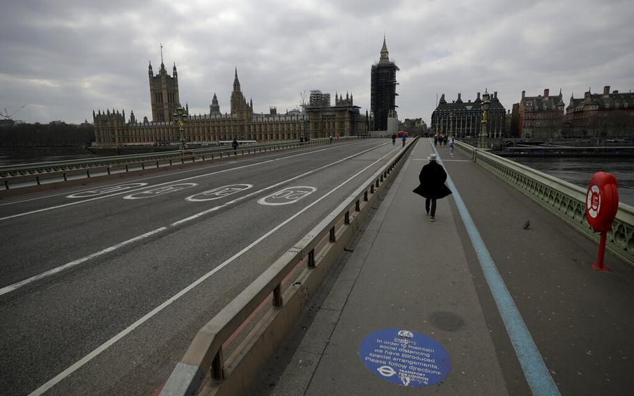 FILE - In this Tuesday, March 23, 2021 file photo, people pass over a quiet Westminster Bridge, backdropped by the scaffolded Houses of Parliament and the Elizabeth Tower, known as Big Ben, in London, during England's third coronavirus lockdown. The British government waited too long to impose a lockdown in the early days of the COVID-19 pandemic, missing a chance to contain the disease and leading to thousands of unnecessary deaths, lawmakers concluded Tuesday, Oct. 12, 2021 in a hard-hitting report.