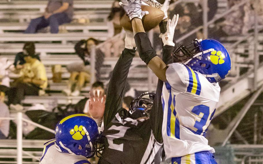 Zama receiver Keshawn McNeill and Yokota defender DeShawn Bryant go up for the ball.
