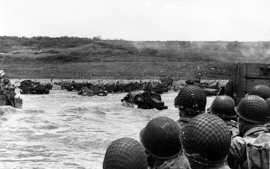Troops watch activity ashore on Omaha Beach as their landing craft approaches on D-Day, June 6, 1944.