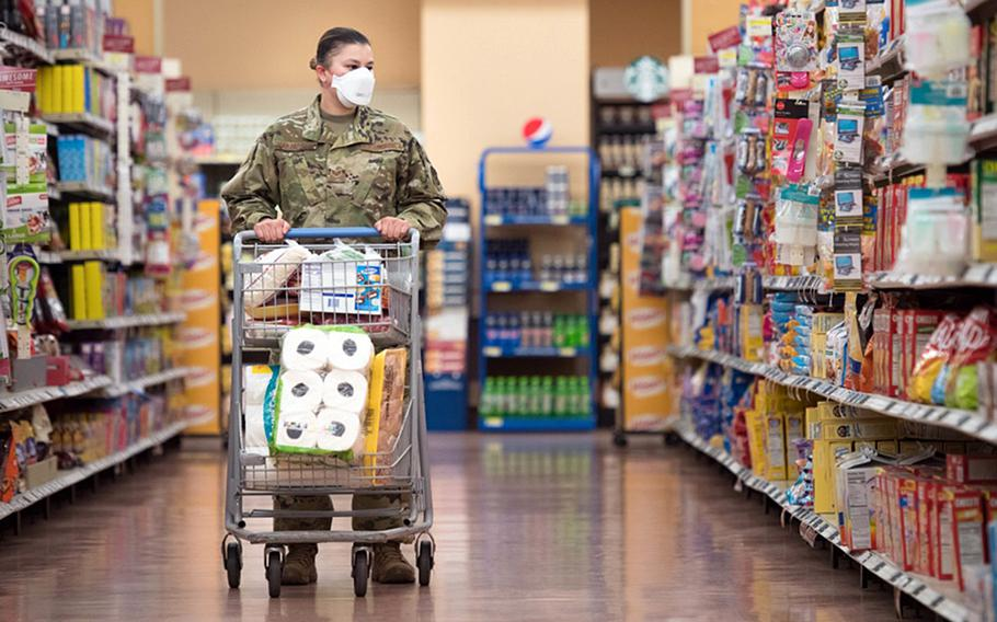 """An airman shops at the RAF Mildenhall, England, commissary. The base is requiring masks to be worn indoors by all, including the fully vaccinated, following a Defense Department directive mandating them where there is """"substantial or high community transmission"""" of the coronavirus."""