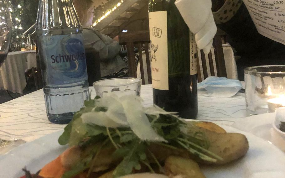 Salmon filet topped with arugula and thinly sliced Italian cheese, served with potatoes and vegetables. The dish was ordered from the prix fixe menu at Julien French restaurant in Kaiserslautern, Germany, on Sept. 1, 2021.