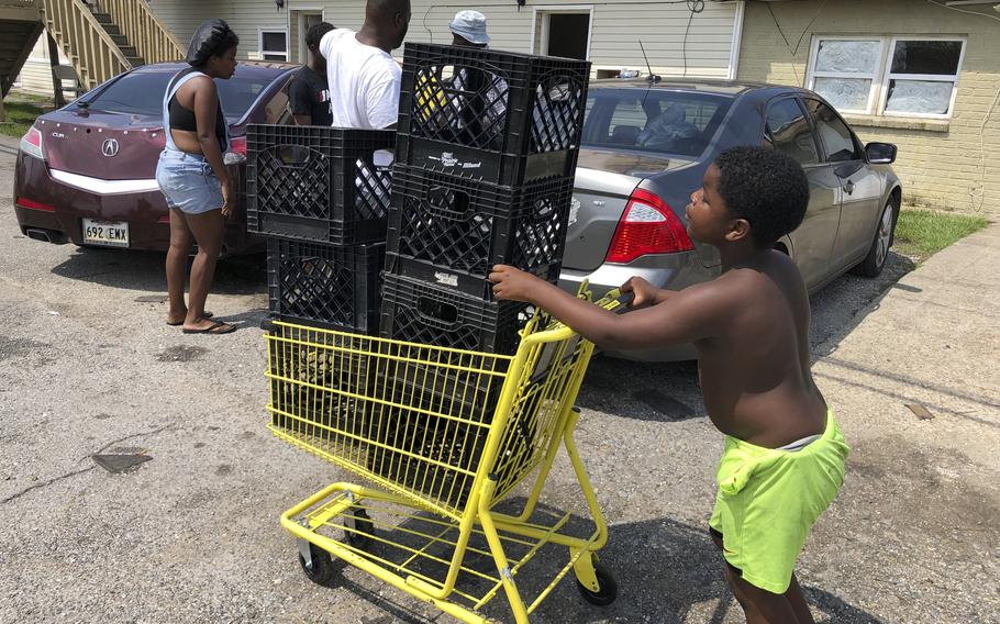 Christopher Williams, 5, pushes a shopping cart outside his family's destroyed apartment in Luling, La., on Tuesday, Sept. 7, 2021. Williams and his two brothers stack milk crates in a vacant parking lot to pass time because their toys were swept away by Hurricane Ida. They are among an estimated 250,000 children across Louisiana with no school to go to after the storm left them shuttered.