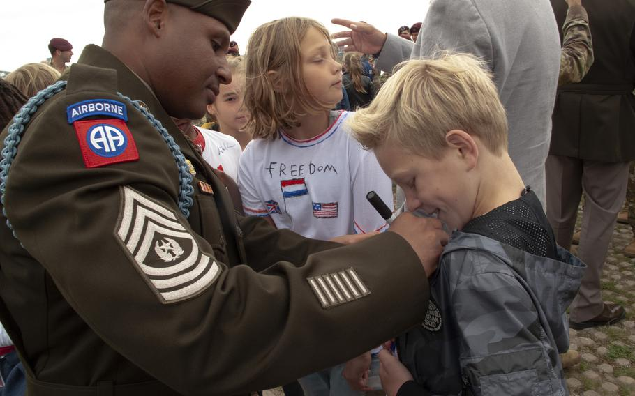 Sgt. Maj. Victor del Valle, left, of the 82nd Airborne Division, signs a Dutch boy's T-shirt at a ceremony in Nijmegen, Netherlands, Sept. 20, 2021, to mark the crossing by U.S. soldiers of the Waal River 77 years earlier.