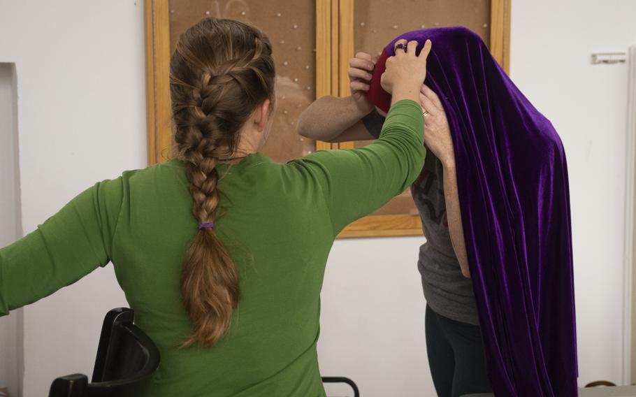 Volunteers try on a prayer garment they made for Afghan refugees at Ramstein Air Base on Aug. 26, 2021.