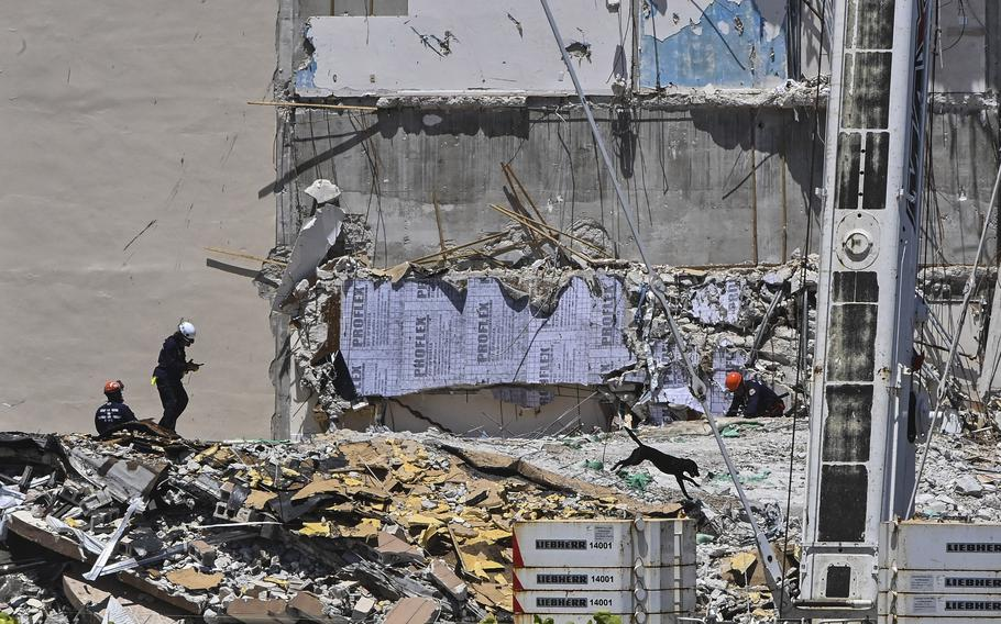 Rescue crew members and their search-and-rescue dog continue to look for survivors Sunday at the collapsed Champlain Towers South condominium building in Surfside, Fla.