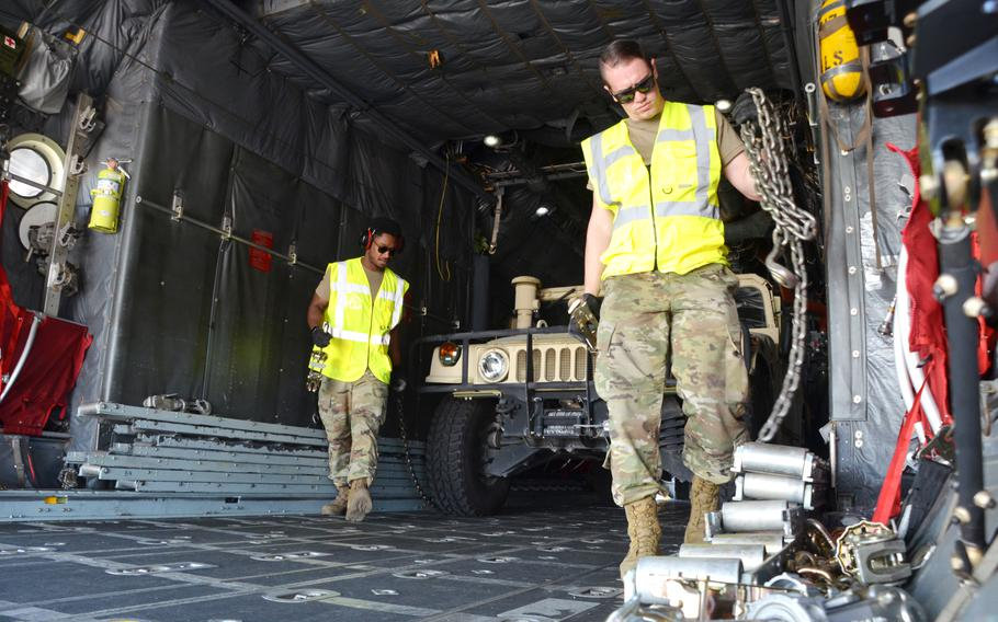 Airmen unchain a Humvee before offloading it from a C-130H as they reconfigure the aircraft for the next team in the 721st Aerial Port Squadron Multi-Capable Airmen Rodeo at Ramstein Air Base, July 23, 2021. Teams of airmen had to load the aircraft safely within 20 minutes in a simulated engine running exercise.