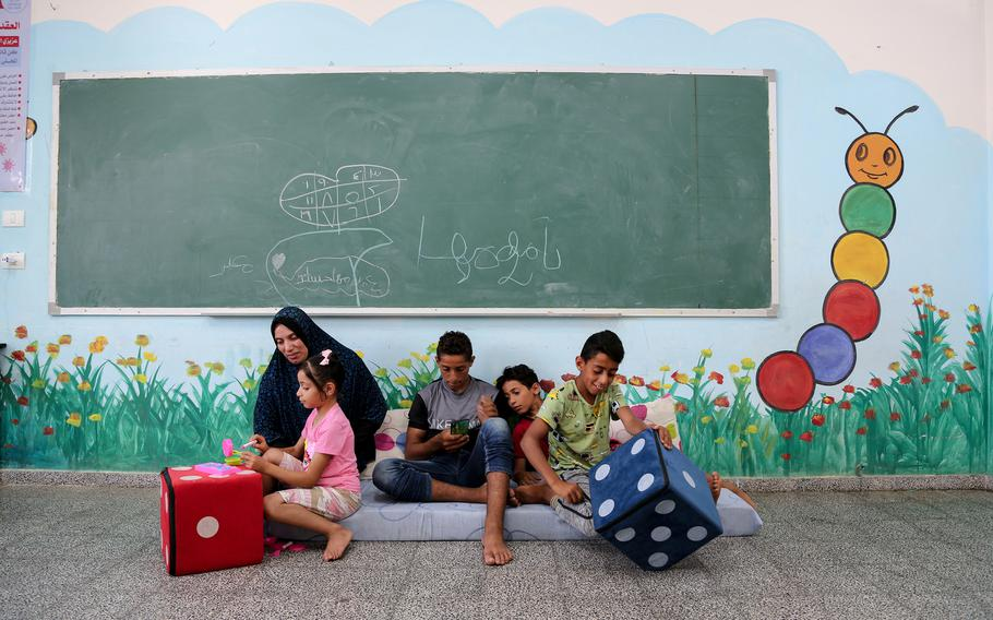 Kowkab Hassanian plays with her children in a school where they took shelter after their house was destroyed in Gaza City.