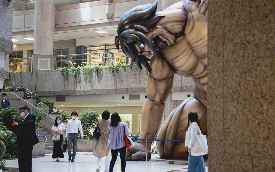 "Visitors to Yokohama Landmark Tower wear masks while passing the ""Attack on Titan"" exhibit in Yokohama, Japan, May 24, 2021."