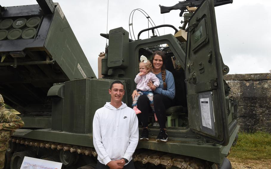 Spc. Christopher Rivera, a wheeled vehicle mechanic with the 41st Field Artillery Brigade, his daughter Olivia, and wife, Melanie Rivera, pose at the unit's family day event at Grafenwoehr Training Area on Aug. 5, 2021.