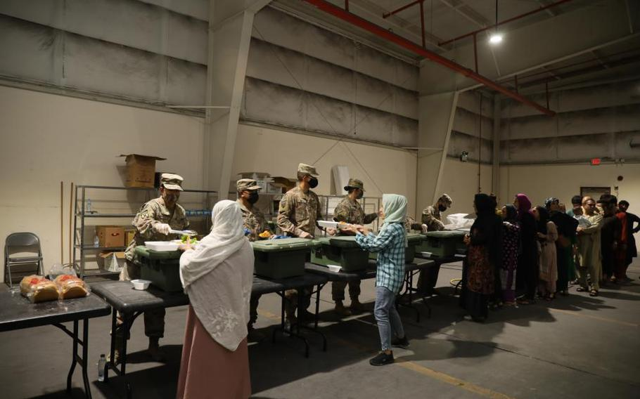 U.S. Army Soldiers serve a lunch meal to Afghan Special Immigrants at a dining facility Tuesday. Soldiers assigned to the facility, prepare and serve meals to Afghan Special Immigrants while they complete Special Immigrant Applications.