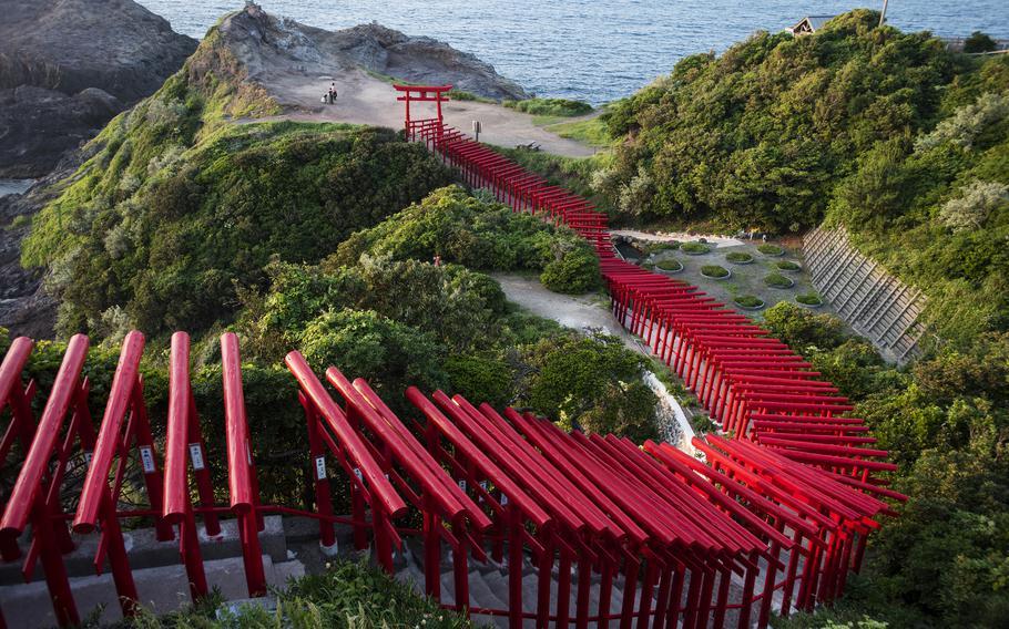 Stroll on a path beneath 123 torii gates toward picturesque sea views during a visit to Motonosumi Inari Shrine in Yamaguchi prefecture, Japan.