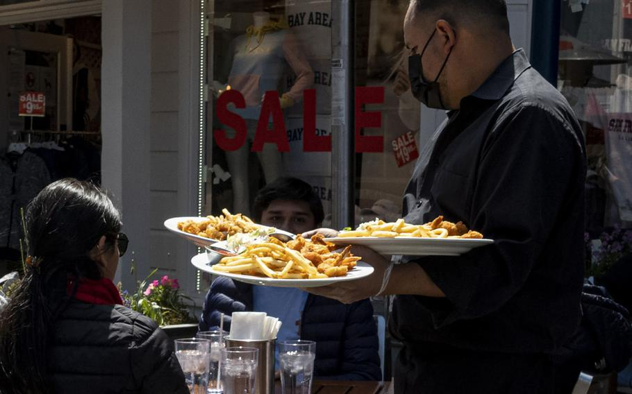 A worker serves food at a restaurant on Pier 39 in San Francisco.