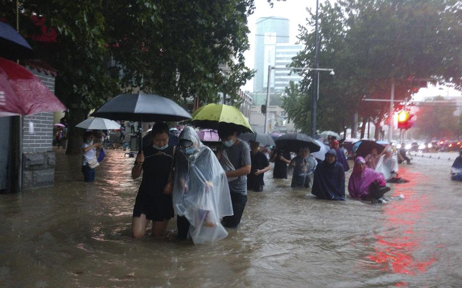 People move through flood water after a heavy downpour in Zhengzhou city in central China's Henan province Tuesday.