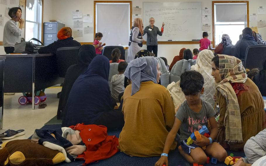 Afghan women and children learn English words in a morning at class at Fort McCoy, Wis., on Sept. 28, 2021.