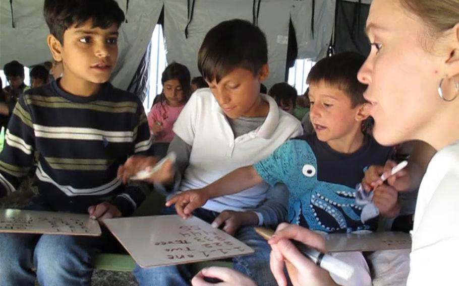 English teacher Morgan Guinn, right, works with three Afghan boys during a writing class at Rhine Ordnance Barracks in Kaiserslautern, Germany, Sept. 27, 2021. Volunteers and soldiers have been introducing the 5,400 Afghans who are temporarily housed at ROB to aspects of American life.