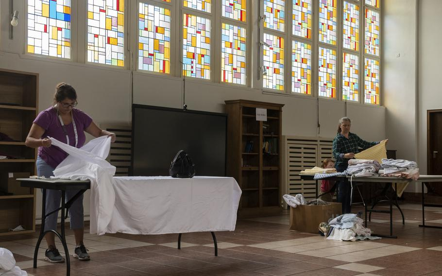 Ann Llams, left, and Maggie Mayfield prepare cloth that volunteers will turn into prayer garments for Afghan refugees at Ramstein Air Base on Aug. 26, 2021.