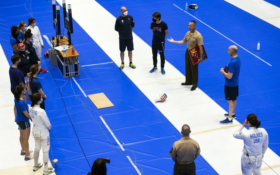 The commander of Marine Corps Air Station Iwakuni, Col. Lance Lewis, presents a gift to the U.S. women's Olympic fencing team at Lotus Culture Center Area, part of the Atago Sports Complex, in Iwakuni, Japan, July 14, 2021.
