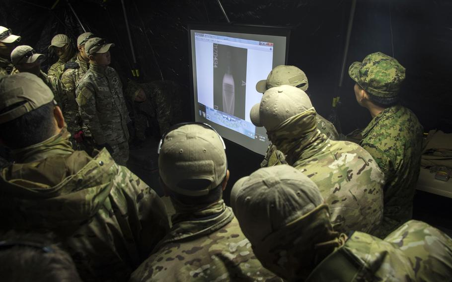 Members of a South Korean navy dive team examine an X-ray image of a possible underwater mine during a Foal Eagle drill in Jinhae, South Korea, March 6, 2017.