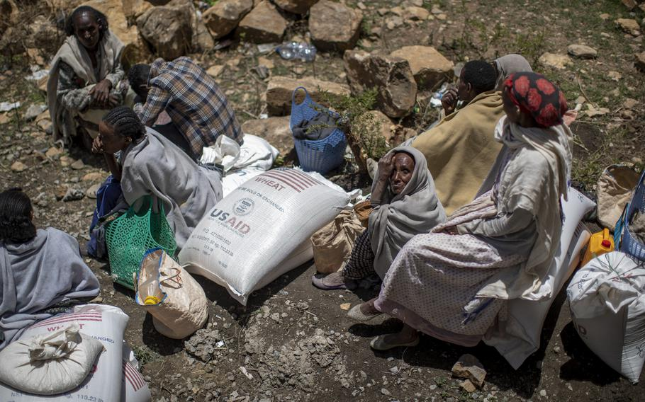 An elderly Ethiopian woman sits next to a sack of wheat after it was distributed to her by the Relief Society of Tigray in the town of Agula, in the Tigray region of northern Ethiopia, on May 8, 2021.