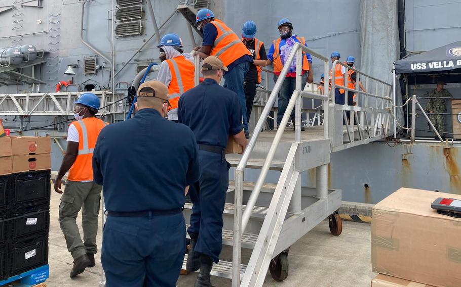 USS Vella Gulf sailors carry on a load of produce as the cruiser prepares to head out to sea again.