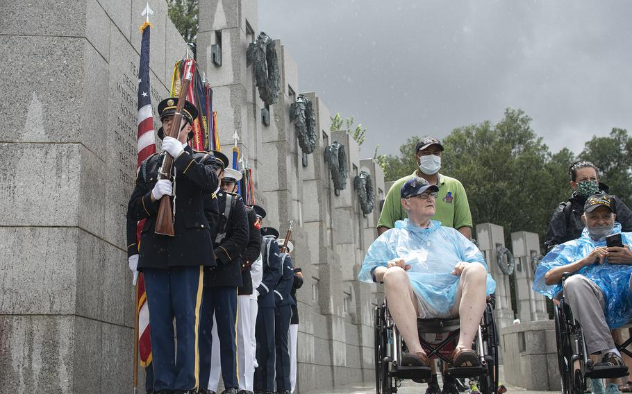 Members of a military honor guard stand at attention as Army veteran Ron Raczak arrives at the World War II Memorial in Washington, D.C., on Wednesday, Aug. 18, 2021, just as a downpour of rain subsides prior to an Honor Flight ceremony that paid tribute to veterans from World War II, the Korean War and the Vietnam War.